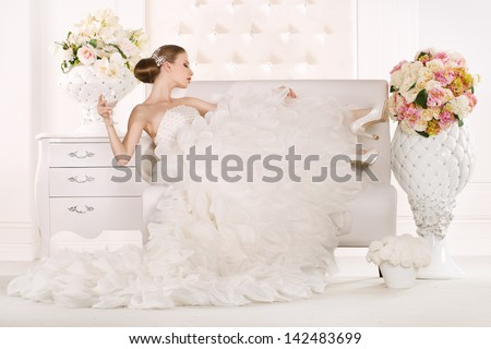 Gorgeous bride standing on sofa