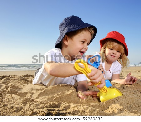 Gorgeous brother and sister ages 4 and 2 have fun digging in the sand at the beach