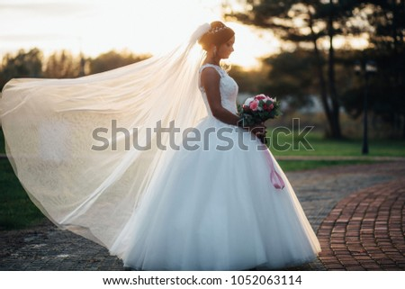 Stock Photo Gorgeous brunette bride poses in the forest with beautiful wedding bouquet in the rays of evening sun