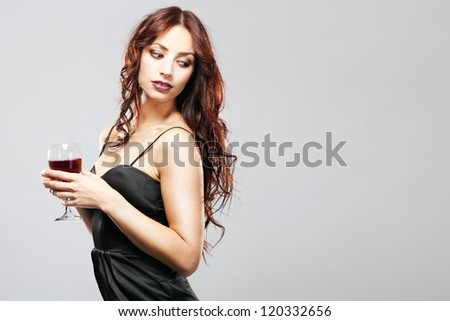 Gorgeous brunette in black dress with a glass of wine