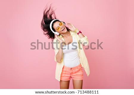 Gorgeous brunette lady in yellow glasses listening music in headphones and singing on pink background. Charming girl in shorts and earphones dancing with hair waving and eyes closed.