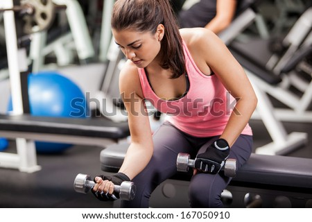 Stock Photo Gorgeous brunette lifting some weights and working on her biceps in a gym
