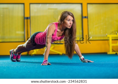 Stock Photo Gorgeous brunette warming up and doing some push ups a the gym