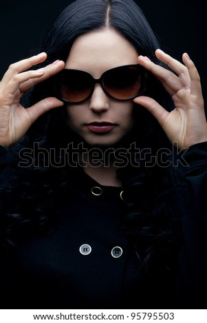 gorgeous brunette wearing sunglasses posing in the studio, low key