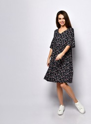 Gorgeous brunette woman with long hair, dressed in black dress with floral print and white sneakers. She is smiling while posing isolated on white. Fashion and beauty concept. Full length, copy space.