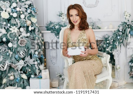 Gorgeous brunette women in a gold evening dress celebrating New Year and Christmas, Beauty Smiling Model Girl holding christmas gift. #1191917431