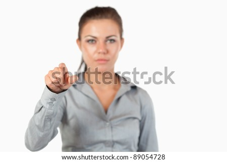 Gorgeous businesswoman pressing an invisible key against a white background
