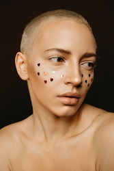 Gorgeous caucasian blonde woman on beauty shot. Hearts on face . Creative make up and perfect skin