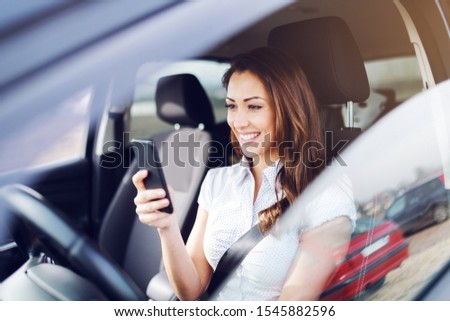 Gorgeous caucasian brunette smiling brunette sitting in her car with safety belt and using smart phone for texting message. #1545882596