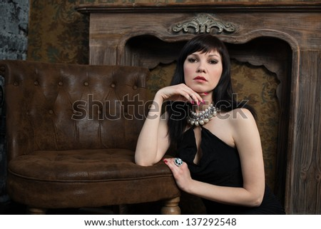 Gorgeous caucasian woman with long dark hair posing in a vintage room, she is wearing black dress and jewelry