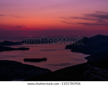 Gorgeous colorful pink and purple sunset and reflections overlooking the islands in the waters of the Adriatic Sea off the coast of Dubrovnik Croatia making a beautiful background image or landscape.