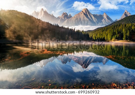 gorgeous composite mountain lake in autumn fog. lovely nature scenery with coniferous forest, rocky peaks and beautiful sky. surface of water reflects the beauty of exquisite landscape.