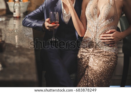 Gorgeous couple in elegant evening dress in front of the bar with glass of wine .  #683878249