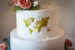 Gorgeous custom travel themed wedding cake with edible world map, pink roses, and message The Adventure Begins