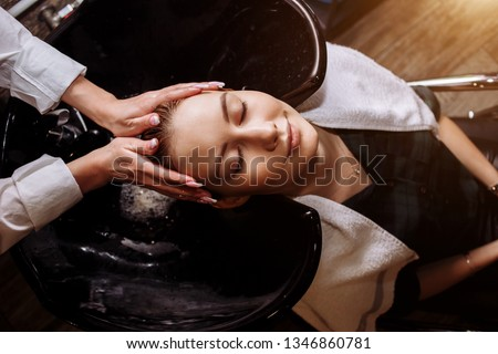 Gorgeous cute young woman enjoying head massage while professional hairdresser applying shampoo her hair. Close up of hairdresser's hands washing hair to the client. Hair Care product.