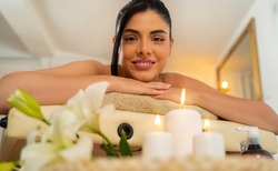 Gorgeous dark hair woman laying on massage table and smiling while looking at camera