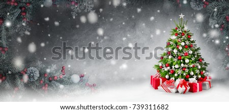 Gorgeous elegant Christmas tree with gifts in red and silver on a panoramic snow background, framed by decorated fir branches #739311682
