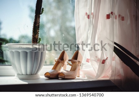 gorgeous elegant stylish beige shoes for bride for a wedding ceremony on the background of light window #1369540700