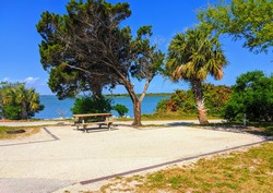 Gorgeous empty waterfront RV camp site spot by turquoise water
