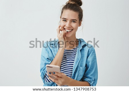 Gorgeous european 25s birthday girl feeling excited happy pleased receiving awesome bday messages holding smartphone smiling happily feeling lucky having devoted awesome friends, looking camera