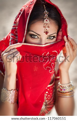 gorgeous eyes of young indian woman in traditional clothing with bridal makeup and jewelry. Beautiful bride traditionally dressed Outdoors in India. Girl bollywood dancer in Sari. Arabian bellydancer