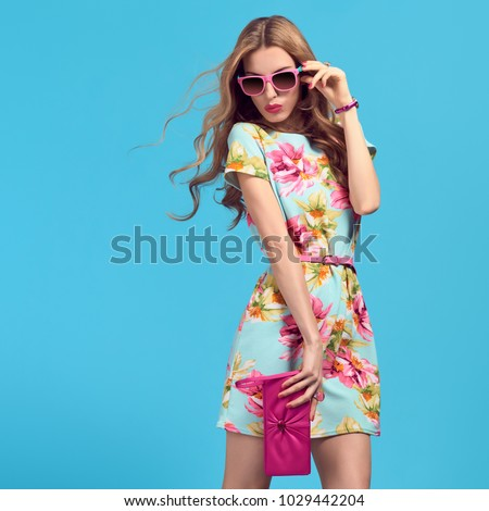 Gorgeous Fashion Blond woman, Trendy Sunglasses. Young female model in Stylish Summer Outfit Posing in Studio. Glamour Long-haired Beautiful Lady. Wavy Hairstyle