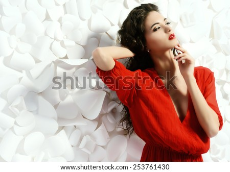 Gorgeous fashion model in bright red dress over background of white paper flowers. Beauty, fashion. Love concept.