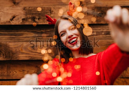 Gorgeous funny girl enjoying new year. Outdoor photo of enthusiastic woman with bengal lights expressing happiness.