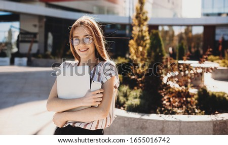 Gorgeous ginger girl with freckles is looking at camera and smiling while holding a laptop and a phone