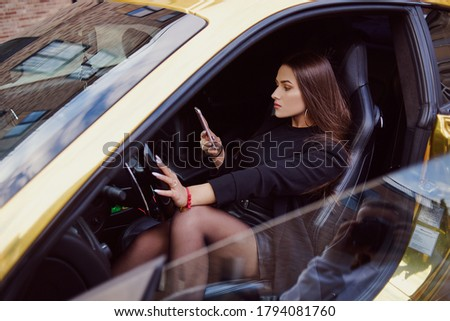 Gorgeous girl in a black outfit sitting in a golden car. A girl holds a phone in her hands, a freelancer girl makes money on the Internet easily. Woman makes a lot of money