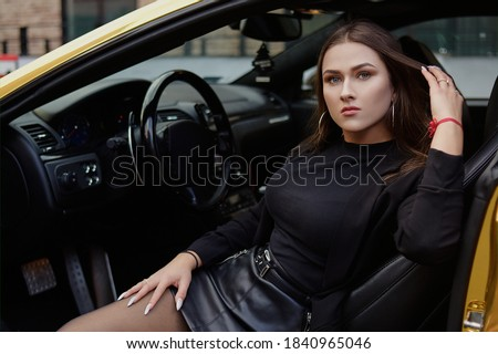 Gorgeous girl in a black outfit sitting in a golden car. Gorgeous brunette in glasses sits. Woman drives an expensive golden car. Successful girl.