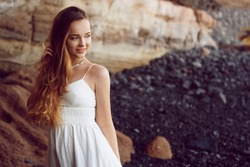 Gorgeous girl in a long white dress on the ocean at the beach. The model is inherited by nature. Girl on vacation, light dress, summer, fashion. Gorgeous long hair develops in the wind. Tenerife