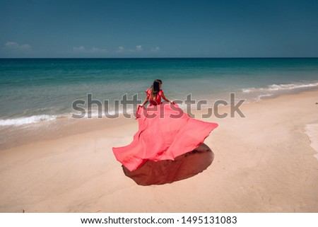 Gorgeous girl in the sunny exotic beach by the ocean. The young woman wears amazing red dress aflutter in the light breeze, backside view; vogue concept.