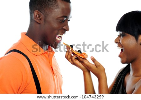 Gorgeous girl offering pizza to handsome guy