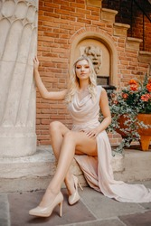 Gorgeous girl sits in a castle on the street on a journey. A blonde in a long delicate dress , on heels, looks at the camera. Model near roses, rich lifestyle.