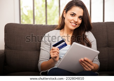 Gorgeous girl using her tablet computer and credit card to buy some stuff online