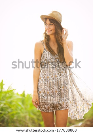 Gorgeous girl walking in the field.  Happy, carefree summer lifestyle.  Woman wearing stylish sun dress.
