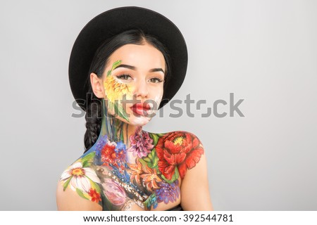 Gorgeous girl with dark long hair wearing black hat, body art paintings on neck, shoulders and face, painting flowers, make up model with naked shoulders.
