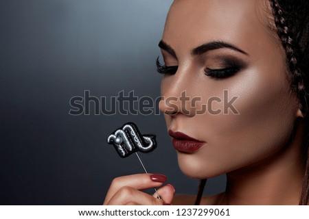 Gorgeous girl with original makeup looks like a Scorpio zodiac sign