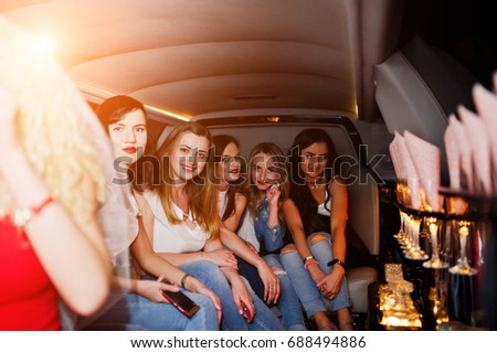 Gorgeous girls having fun while sitting inside the luxurious limousin at bachelorette party.