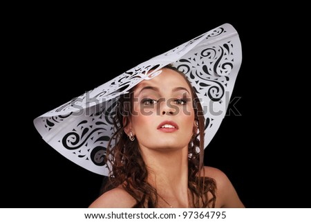 Gorgeous glamour woman close up in big white paper hat isolated over black background