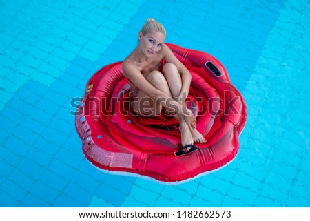 Gorgeous gorgeous lady in red bathing suits on an air mattress a red rose swims in the pool of an elegant hotel, summer vacation, happiness, travel, smiles, joy, top view
