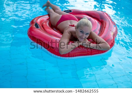 Gorgeous gorgeous woman in a reddish bathing suit on a weightless mattress a red rose swims in the pool of an elegant hotel, summer vacation, happiness, travel, smiles, joy, top view