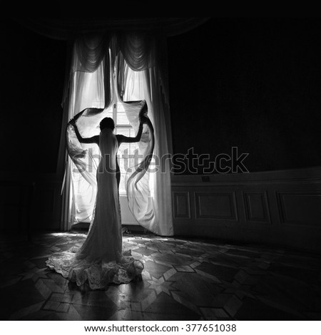 Gorgeous happy bride in white dress opening curtains in theatre b&w