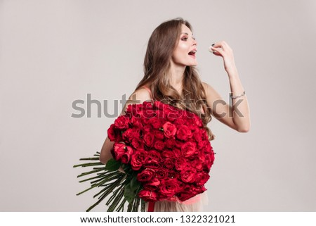 Gorgeous happy brunette with long wavy hair holding beautiful red roses bunch and eating delicious dessert with her hand. Isolated on white background in studio.