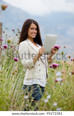 Gorgeous Hispanic-American model uses smiles while holding a tablet pc. Mountains appear faintly in the background.