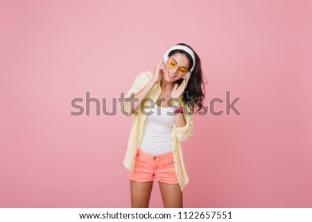 Gorgeous hispanic woman in trendy wristwatch listening music with eyes closed. Indoor portrait of amazing latin female model in pink shorts enjoying song on studio photoshoot. #1122657551