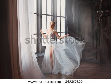 Photo of gorgeous image of graduate in 2019, girl in long white light gentle flying dress with bare leg stands alone, swan princess before performing on ballet stage, elegant lady with blond hair in sunlight