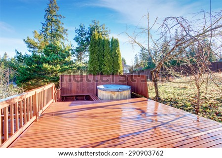 Gorgeous large back patio with red wooden deck. #290903762