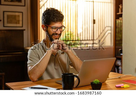 Gorgeous latin laughing during video conference. Home office concept.